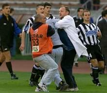 Član redarske ekipe i lekar pomažu jednom od povređenih navijača